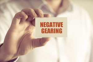 Person holding small card reading Negative Gearing