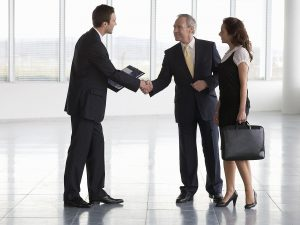 commercial property agent greeting business man and business woman